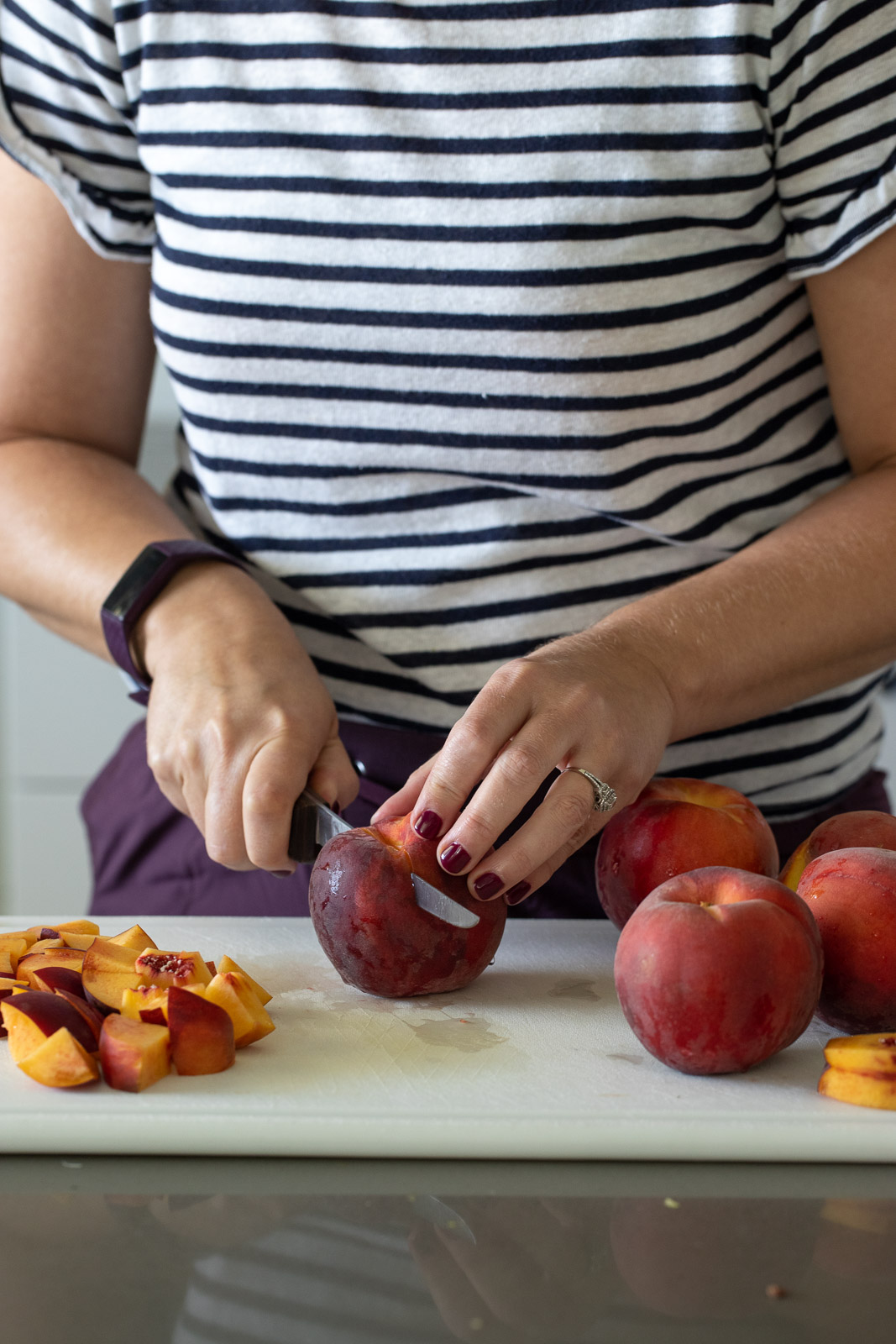 Woman slicing peaches on a white cutting board.