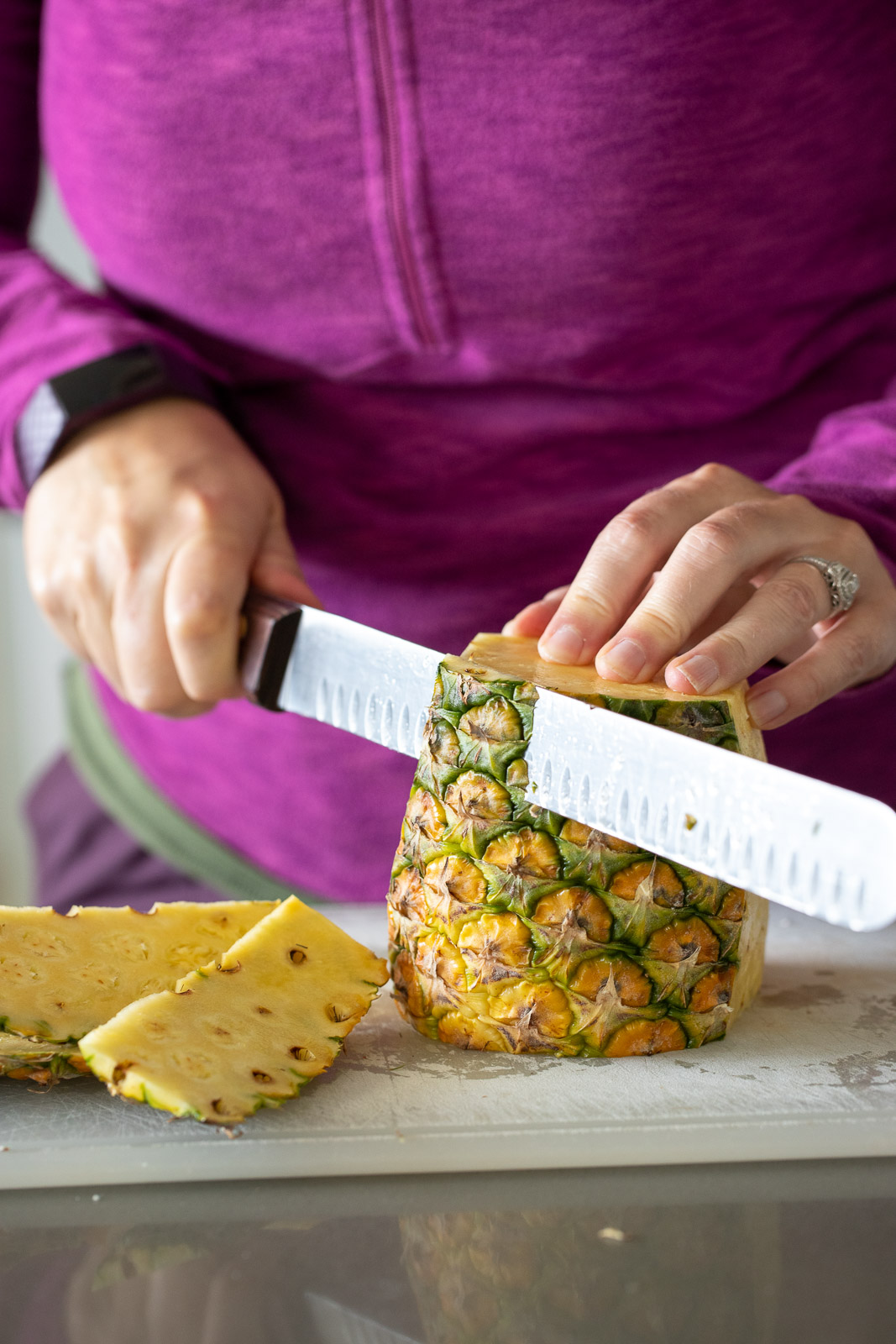 woman cutting up fresh pineapple on a plastic cutting board.