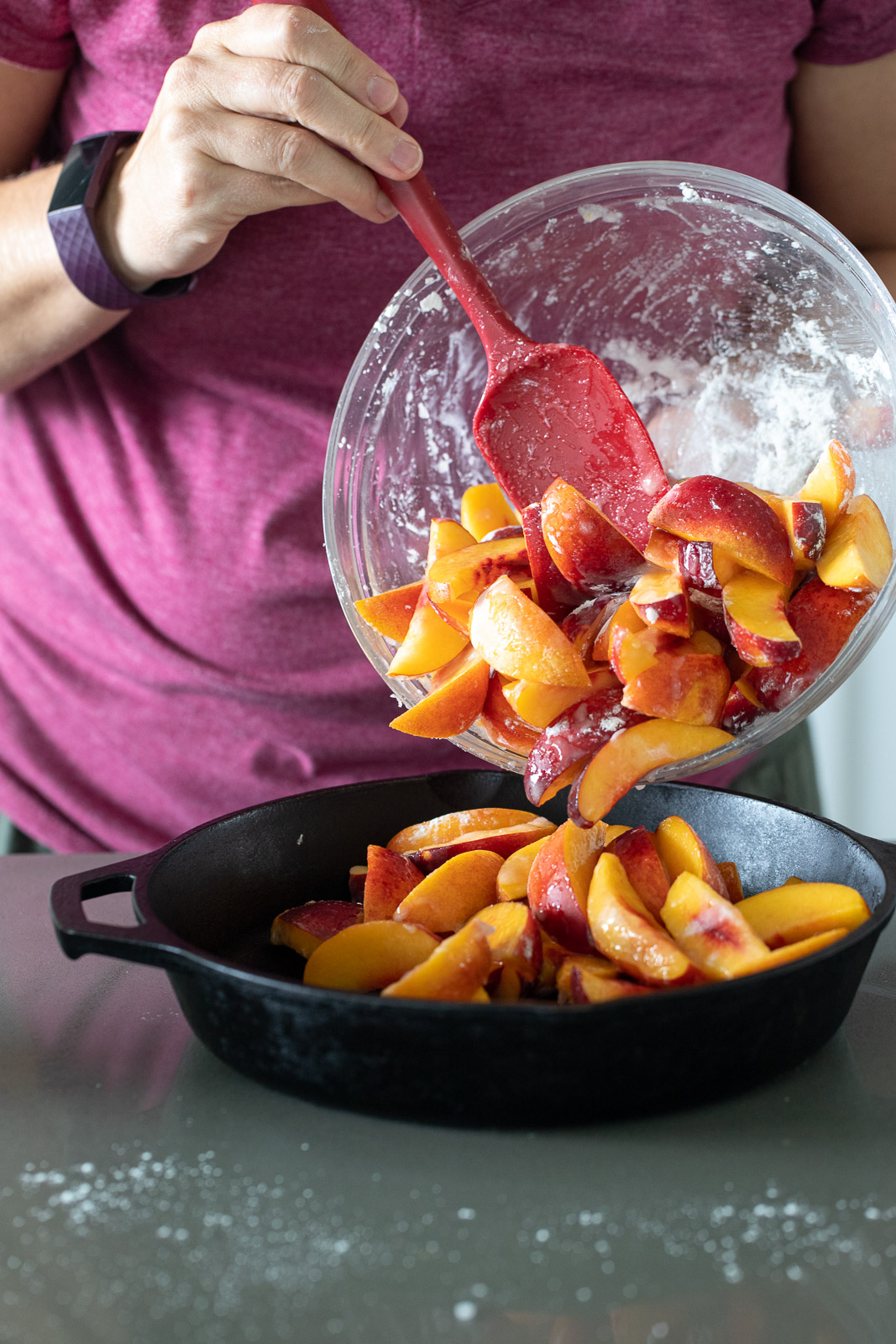 woman pouring nectarines into a cast iron skillet.