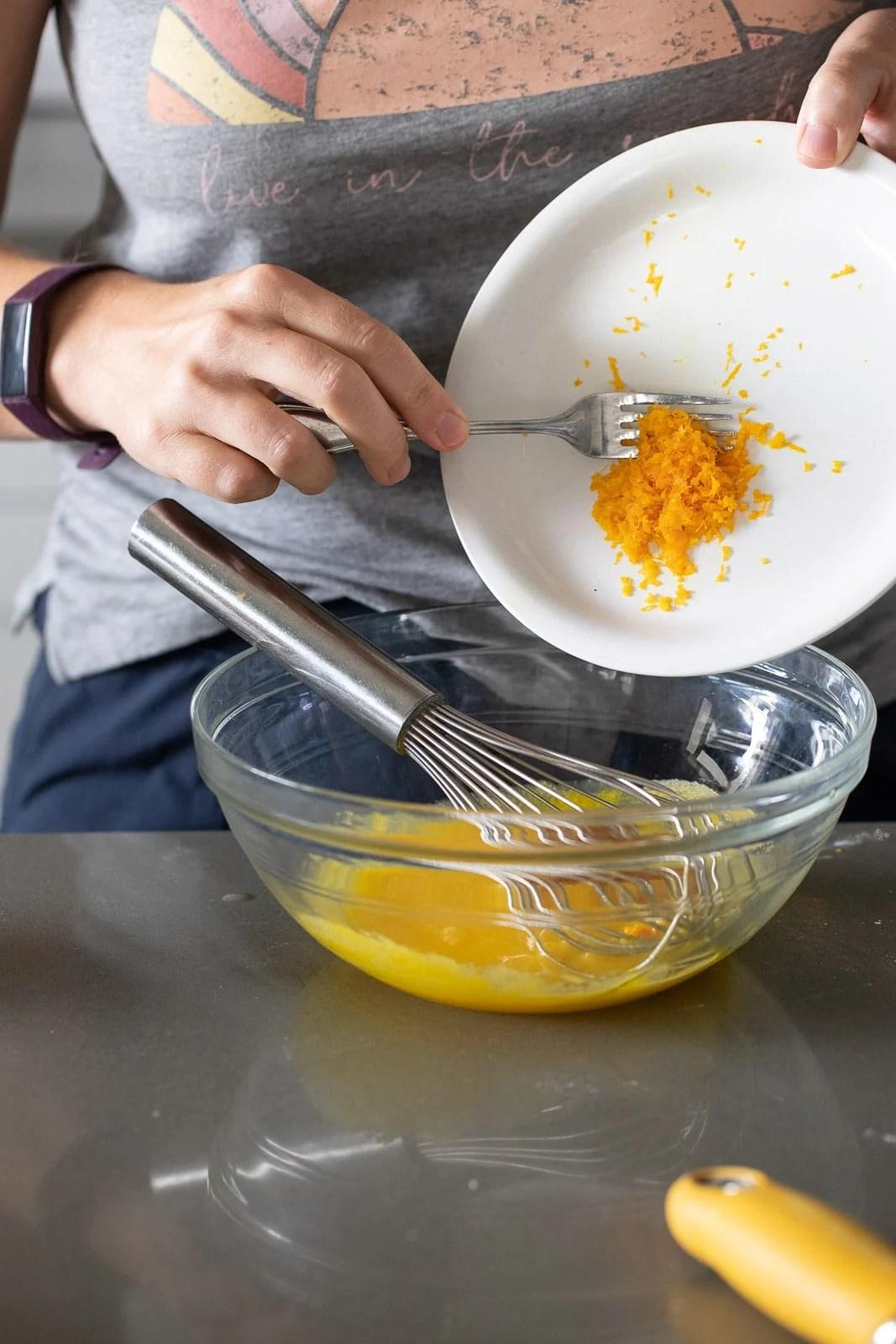 woman adding orange zest to egg yolks.