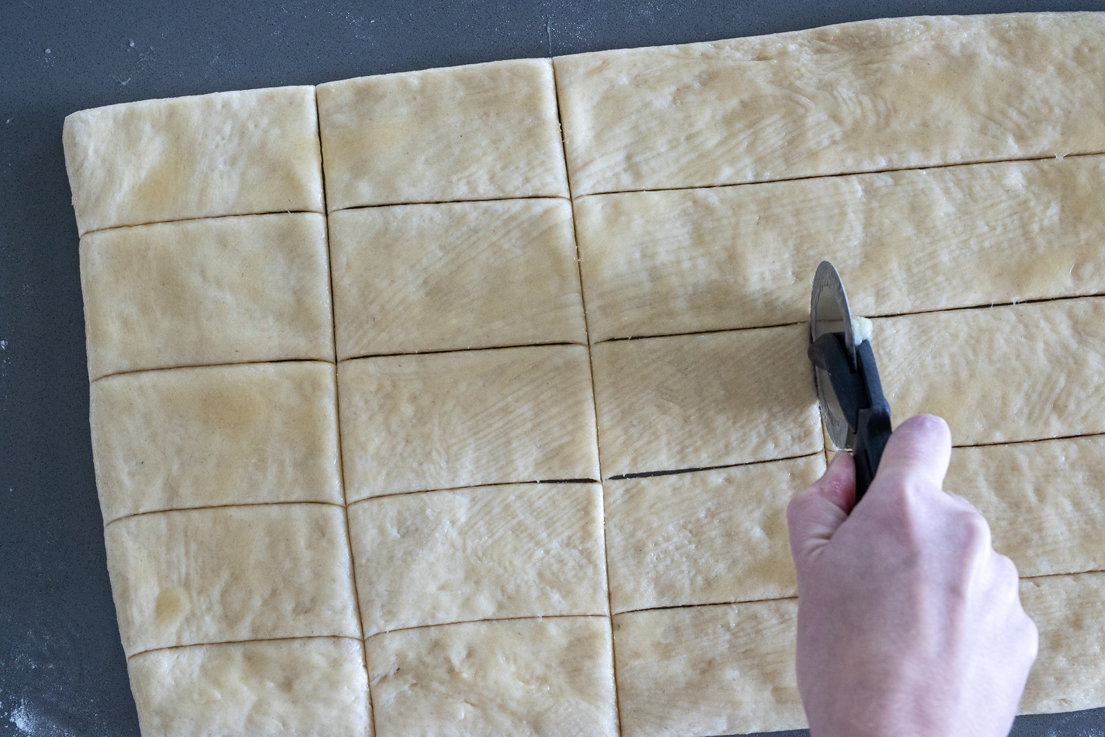 Woman cutting Parker House Rolls into rectangles for baking.