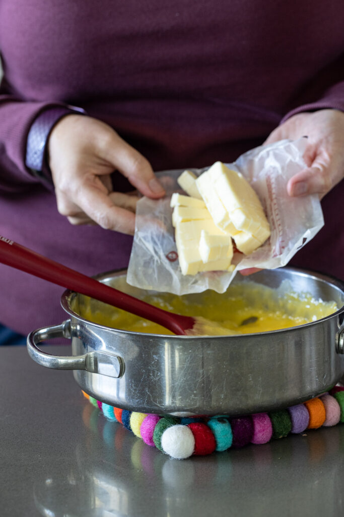 Woman adding butter to lemon curd.