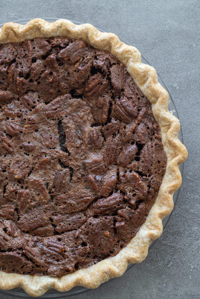 Chocolate pecan pie in a pan on a surface.