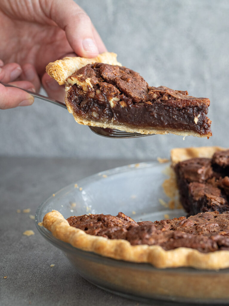 Woman taking a piece of chocolate pecan pie from a pan.