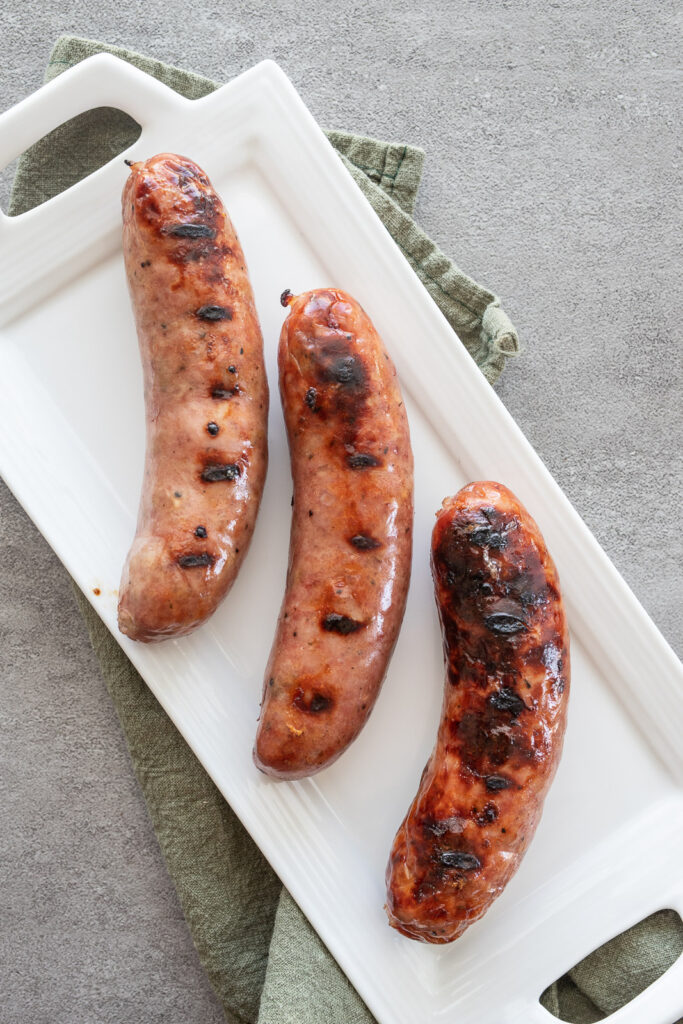 Grilled Chicken sausage on a white platter with a green napkin underneath.