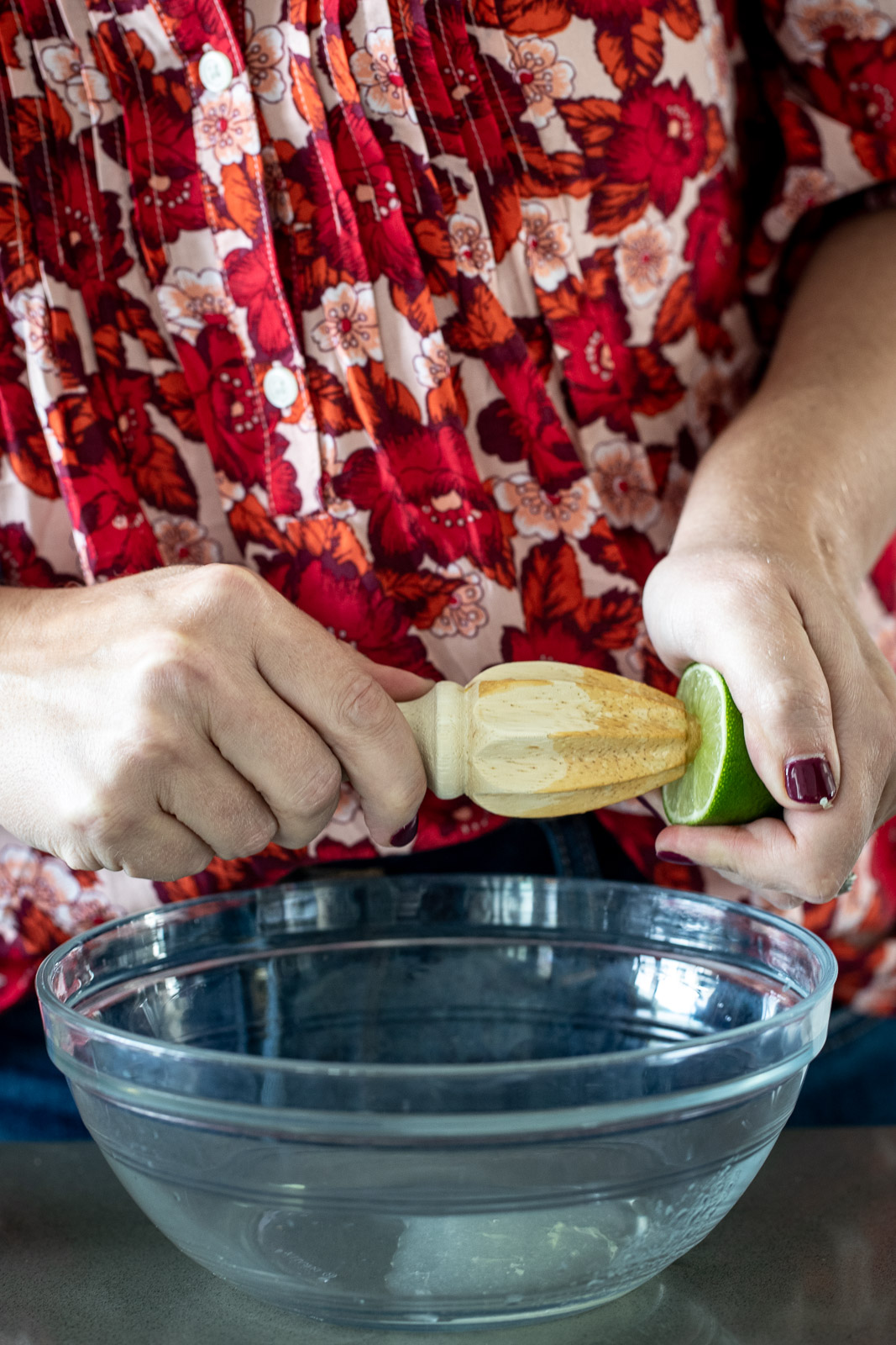 Woman juicing lime into a glass bowl.