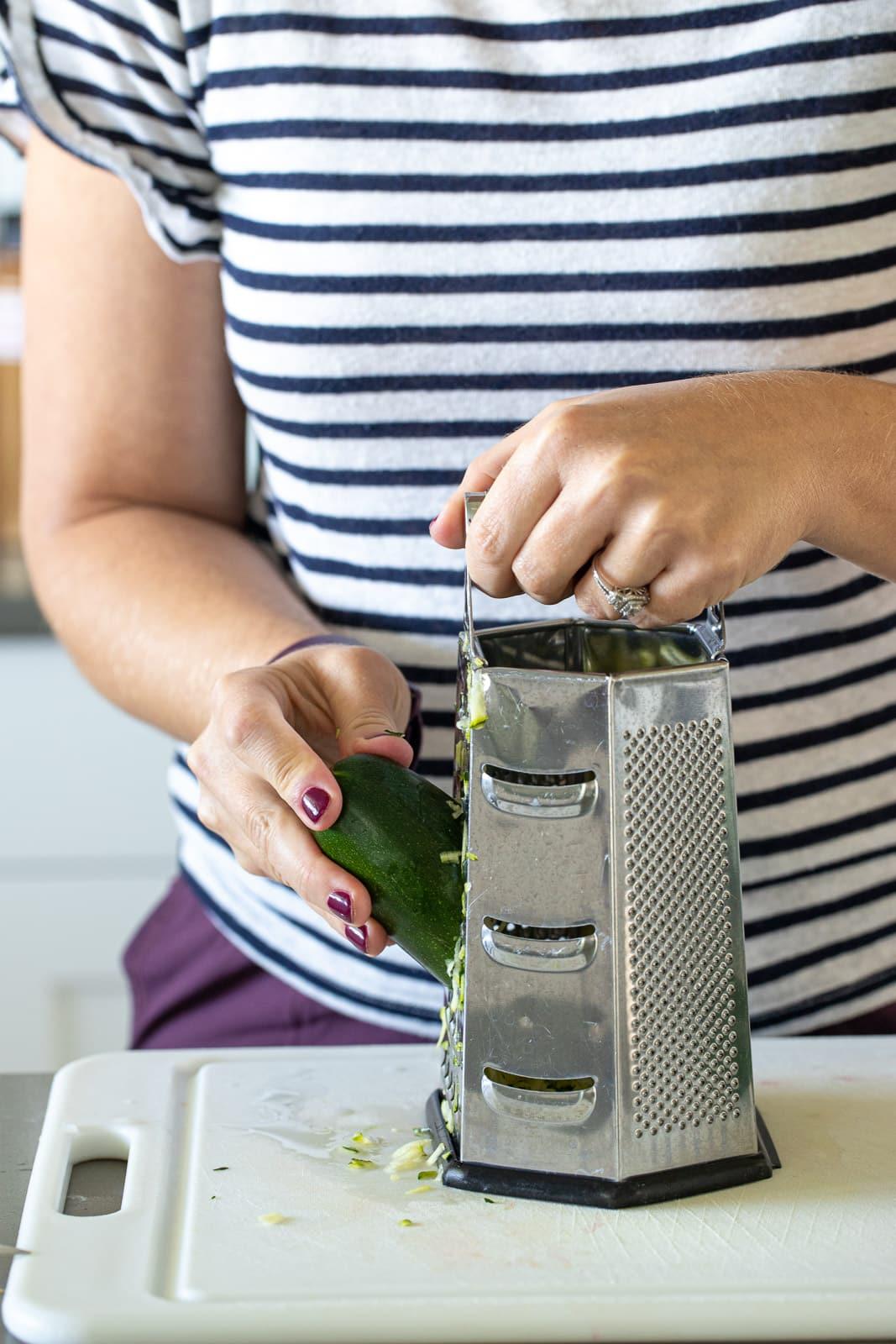 woman grating zucchini for zucchini bread.