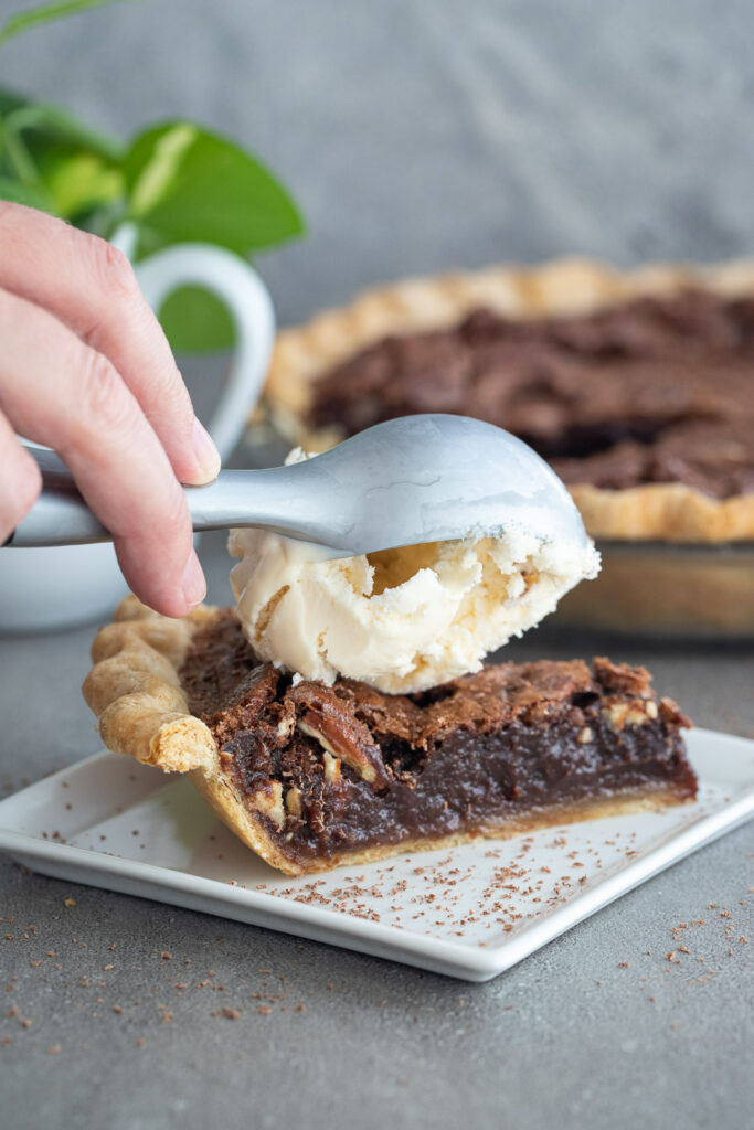 Woman scooping ice cream on top of a piece of pie.