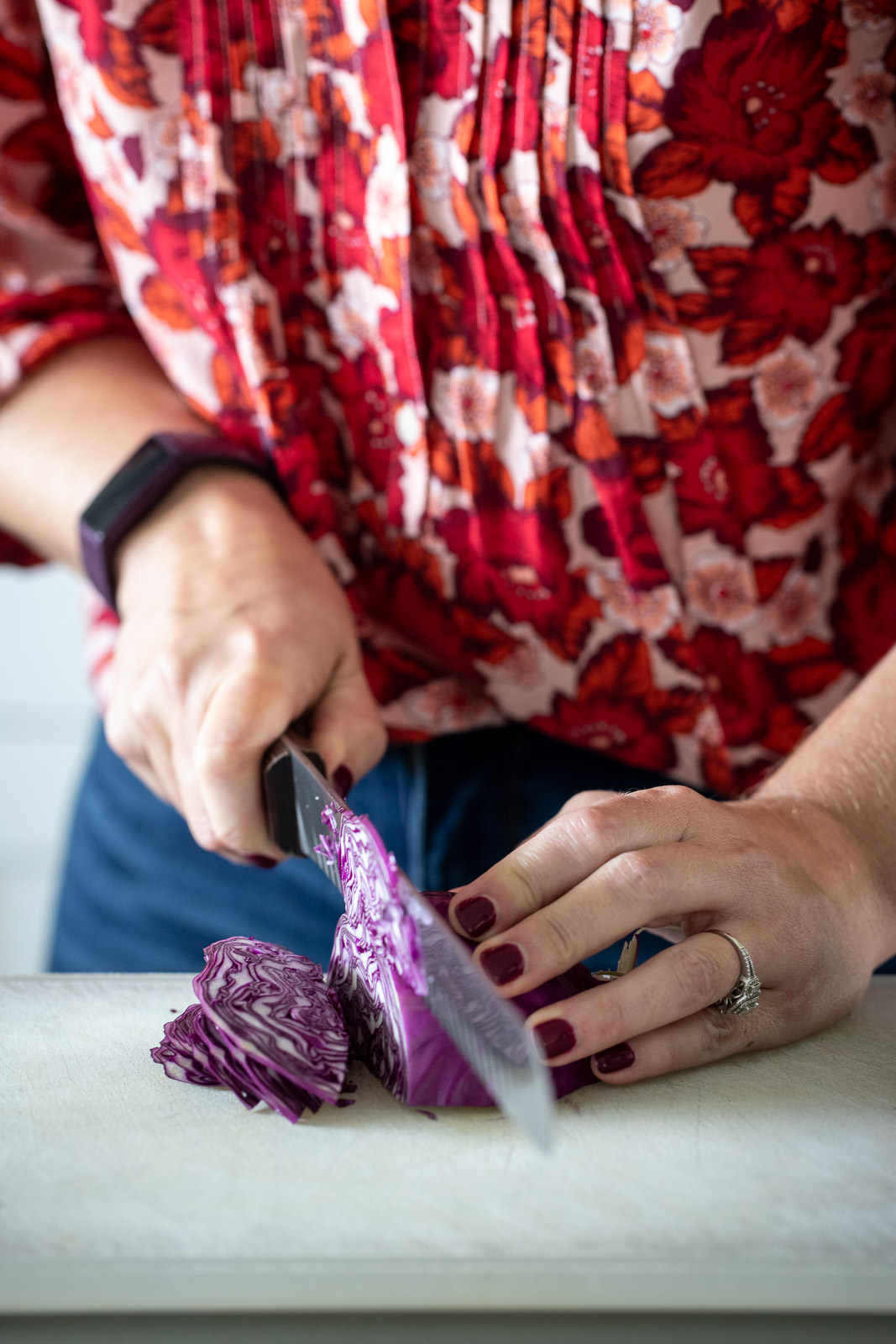 Woman slicing red cabbage on a plastic cutting board.