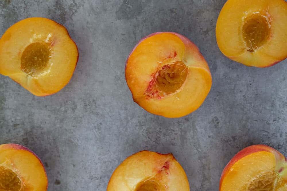 Peaches cut in half on a baking sheet.