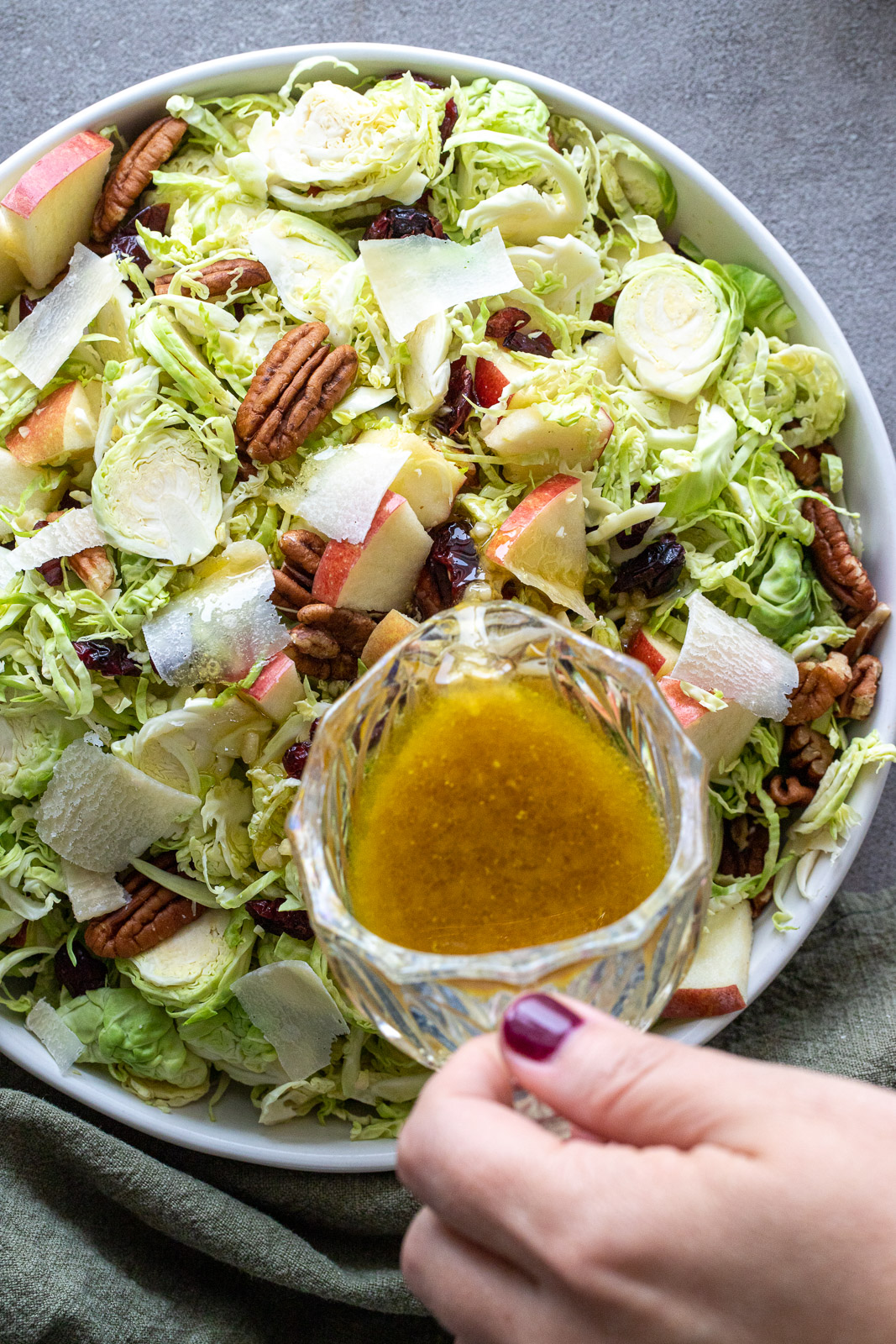 Woman pouring maple dressing over a brussel sprouts salad.