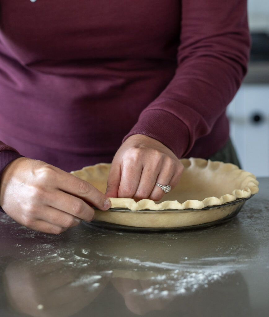 Woman crimping pie shell.