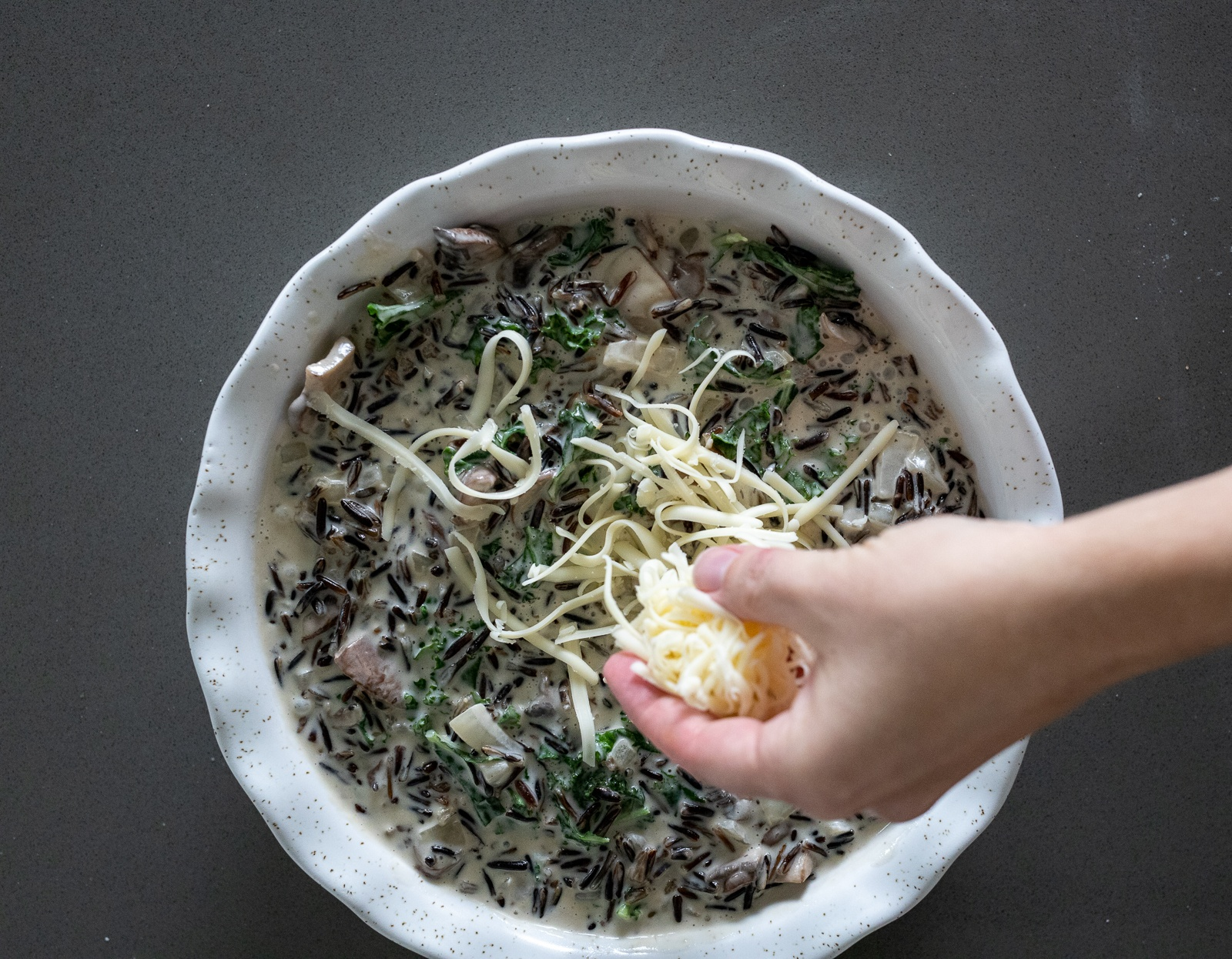 Wild rice casserole with mushroom being topped with gruyere.