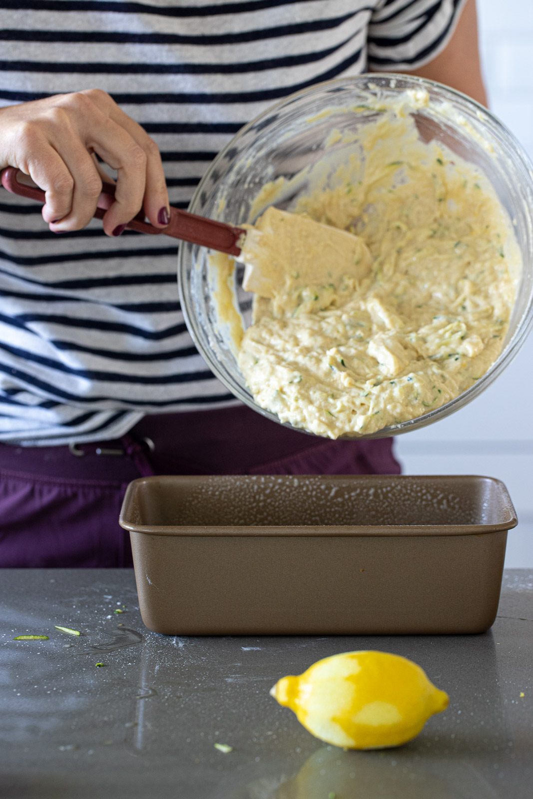 Woman pouring lemon zucchini bread batter into a bread pan.