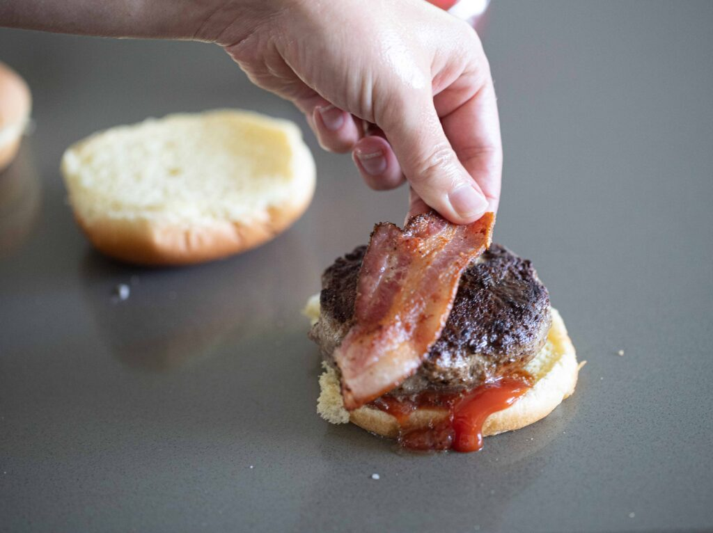 Woman placing sliced of cooked bacon on a hamburger.