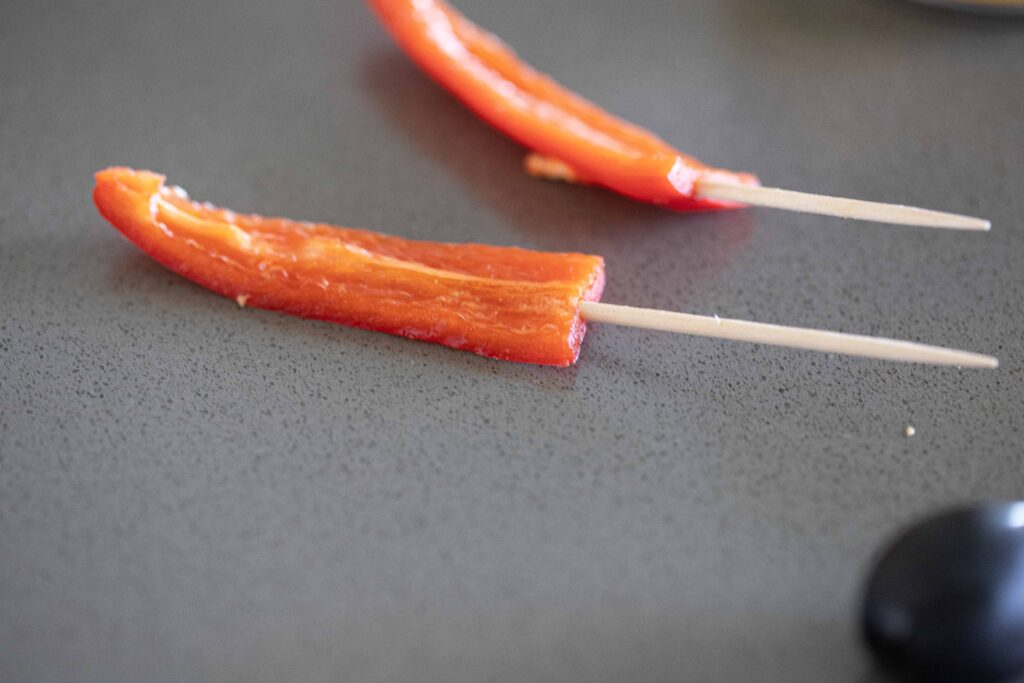 Bell peppers cut into strips and placed on a toothpick.
