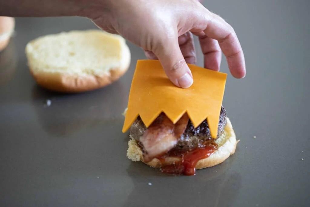Woman placing cheese sliced on a hamburger bun.