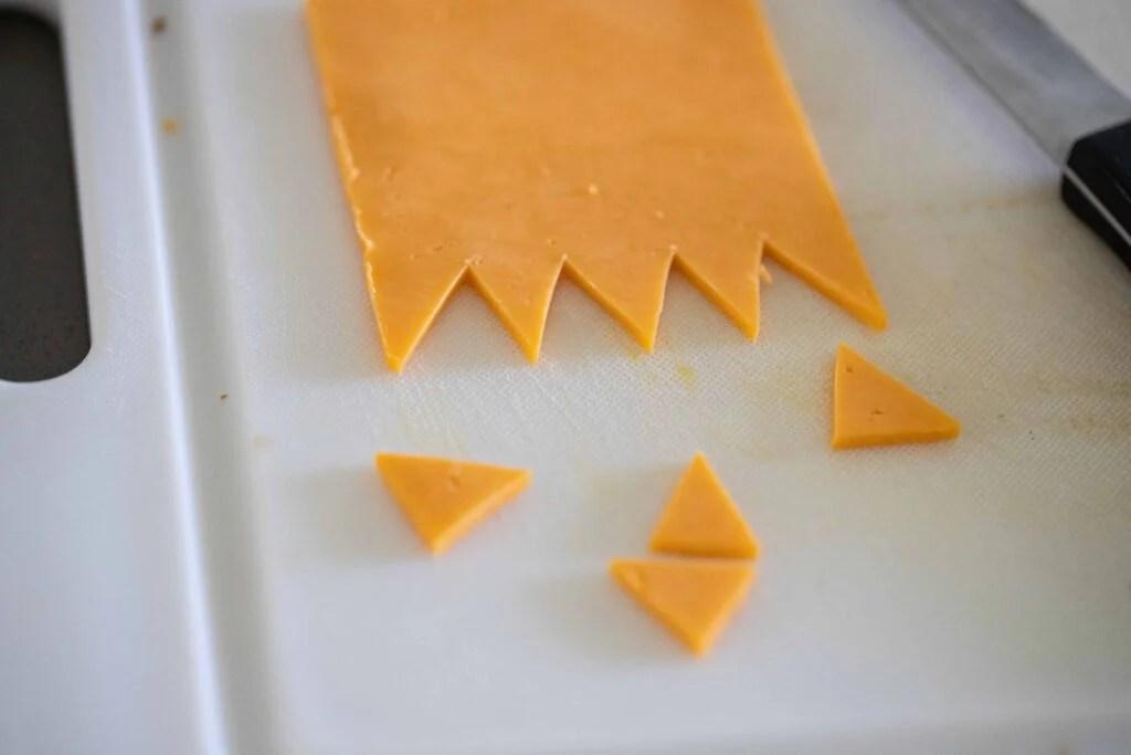 Slices of cheddar cheese cut on a plastic cutting board.