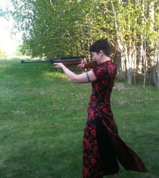 Arga Klara skjuter med luftgevär. Fest för bästa M med utmaningar! Svart och röd kinesisk klänning.