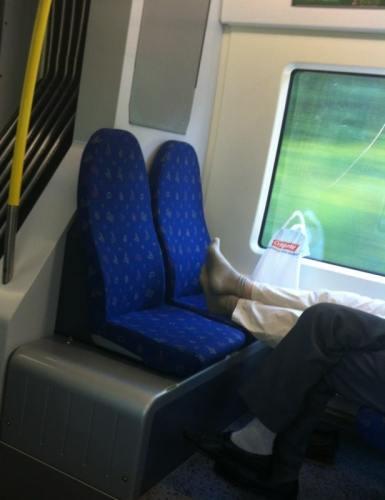 Fötter på sätet på pendeltåget