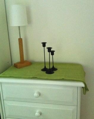 Grön duk med lampa och ljusstakar på vit byrå