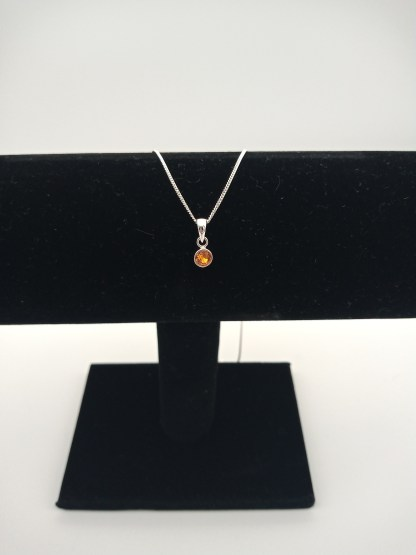 925 silver orange cz birthstone pendant on jewellery stand