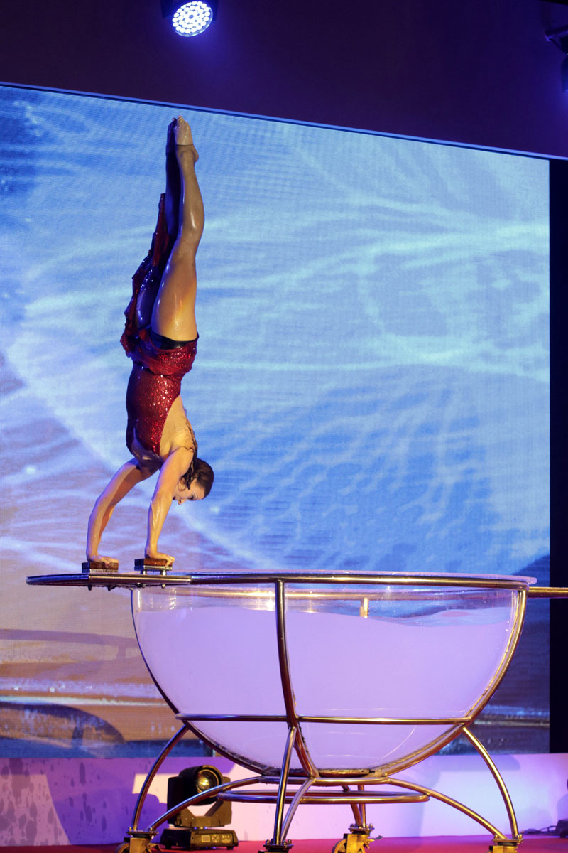 acrobat in handbalance pose - water bowl show - Argolla corporate entertainment