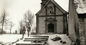 At 1300 hours, after three days of battle, this town was finally retaken. Yanks surrounded the Germans after losing the town during initial German counter attack. The patrol is about to enter the the church to examine the belfry and cellar where snipers are still believed to be hiding. American prisoners where held here.