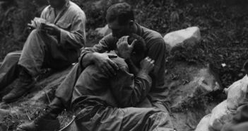 A soldier comforts his buddy in World War II. (Credits: National Archives)
