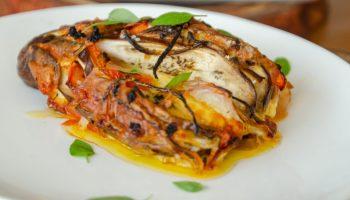 berinjela assada, fatiada como leque e recheada com queijo, tomate e cebola em um prato branco sobre a mesa