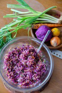 salada de repolho roxo sobre mesa de madeira juntos de uma faca e ingredientes da receita