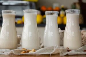4 garrafas transparentes com leites vegetais sobre a mesa