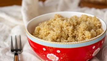 bowl vermelho sobre toalha branca com quinoa cozida dentro