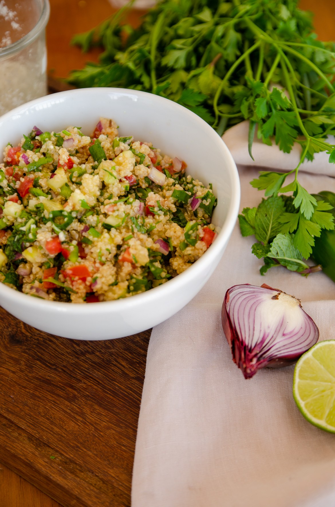 Salada tabule de quinoa em um bowl branco sobre uma mesa de madeira, ao lado os temperos utilizados na receita, limão, cebola e cheiro verde