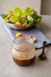 No primeiro plano temos um pote de vidro com o molho para saladas asiático, logo atrás uma salada de folhas verdes, ovos de codorna, tomate cereja e algumas torradinhas em um prato bege sobre um guardanapo de tecido listrado preto e branco