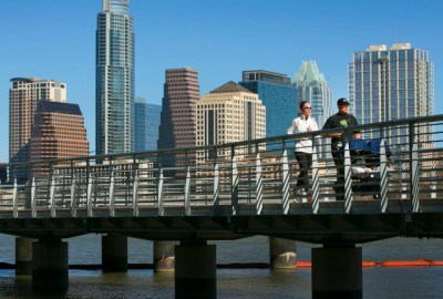 Diedra and Ryan Smith enjoy the brisk morning weather with a run along the Boardwalk on Lady Bird Lake with their daughter Stella, 2, in tow as the city skyline provides a dramatic backdrop. RALPH BARRERA/ AMERICAN-STATESMAN