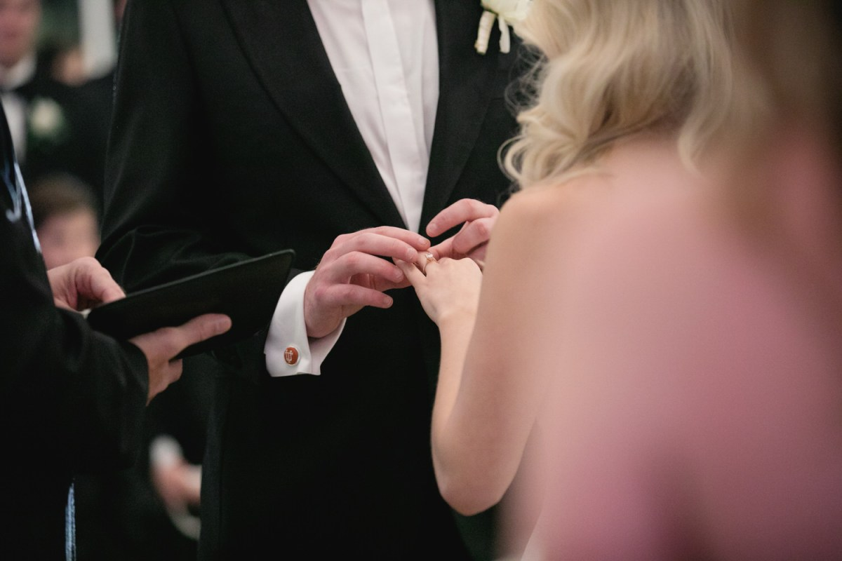 groom places ring on brides hand