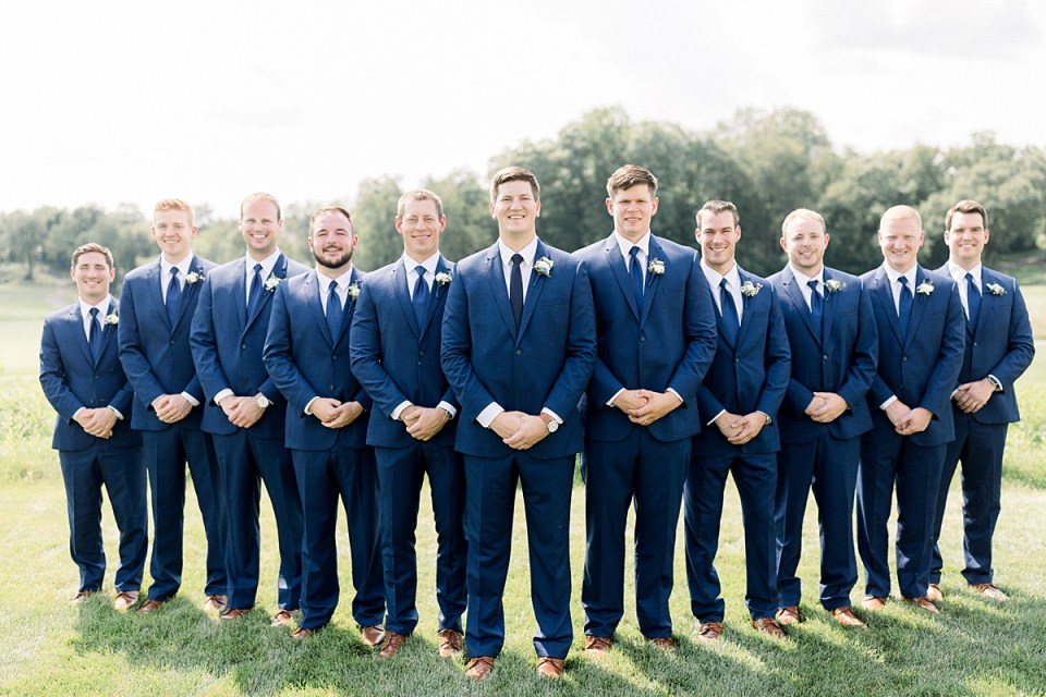 Arielle Peters Photography | Groom and groomsmen lined up smiling at The Blue Heron at Blackthorn in South Bend, Indiana on wedding day.