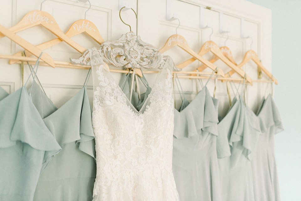 Arielle Peters Photography | Wedding gown hanging next to bridesmaids dresses at Sycamore Hills Golf Club in Fort Wayne, Indiana on wedding day.