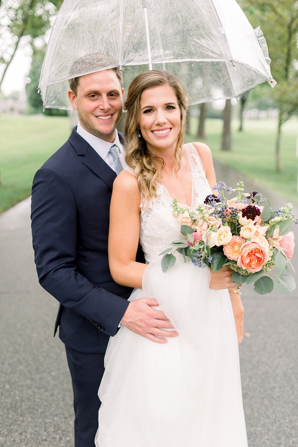Arielle Peters Photography | Bride and groom smiling in the rain outside on wedding day at Sycamore Hills Golf Club in Fort Wayne, Indiana.