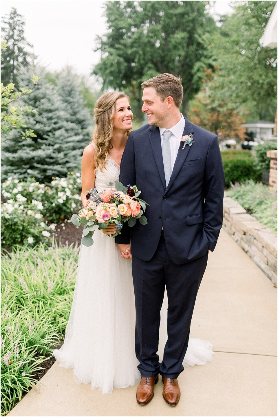 Arielle Peters Photography | Bride and groom walking outside in the rain at Sycamore Hills Golf Club in Fort Wayne, Indiana on wedding day.