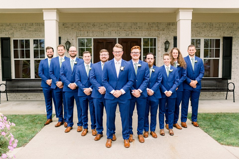 Arielle Peters Photography | Groom and groomsmen smiling outside in their tuxes at The Bridgewater Club in Carmel, Indiana on wedding day.