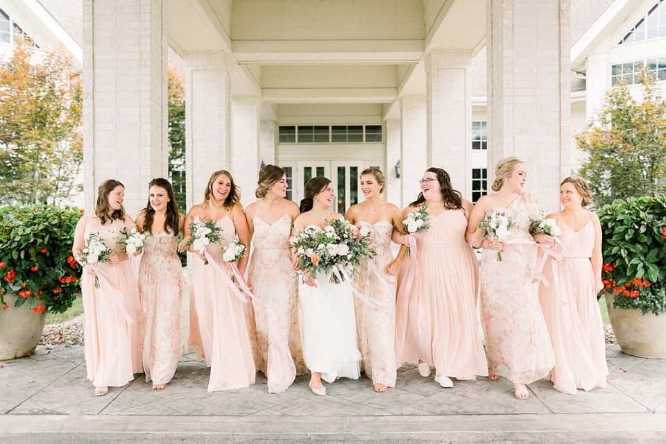 Arielle Peters Photography | Bride and bridesmaids walking and smiling outside at The Bridgewater Club in Carmel, Indiana on wedding day.