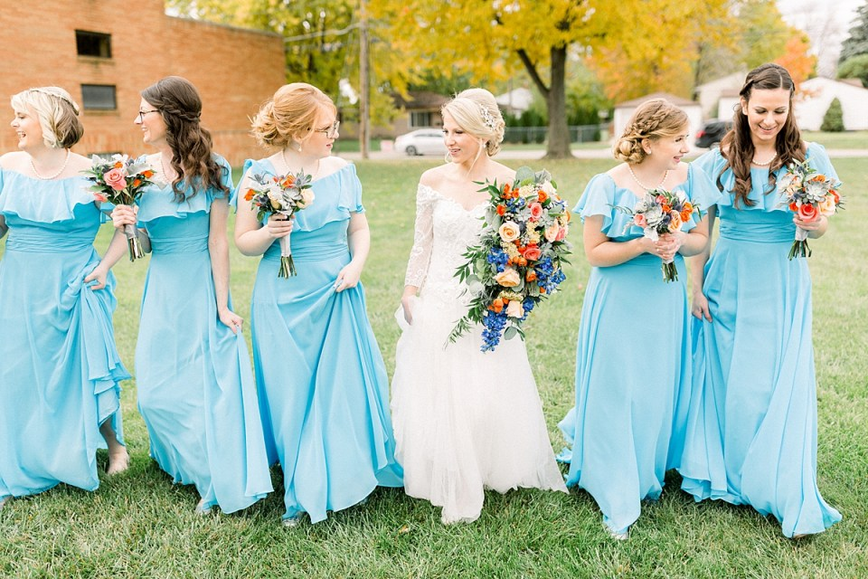 Arielle Peters Photography | Bride and bridesmaids walking with bouquets and smiling outside on fall wedding day.
