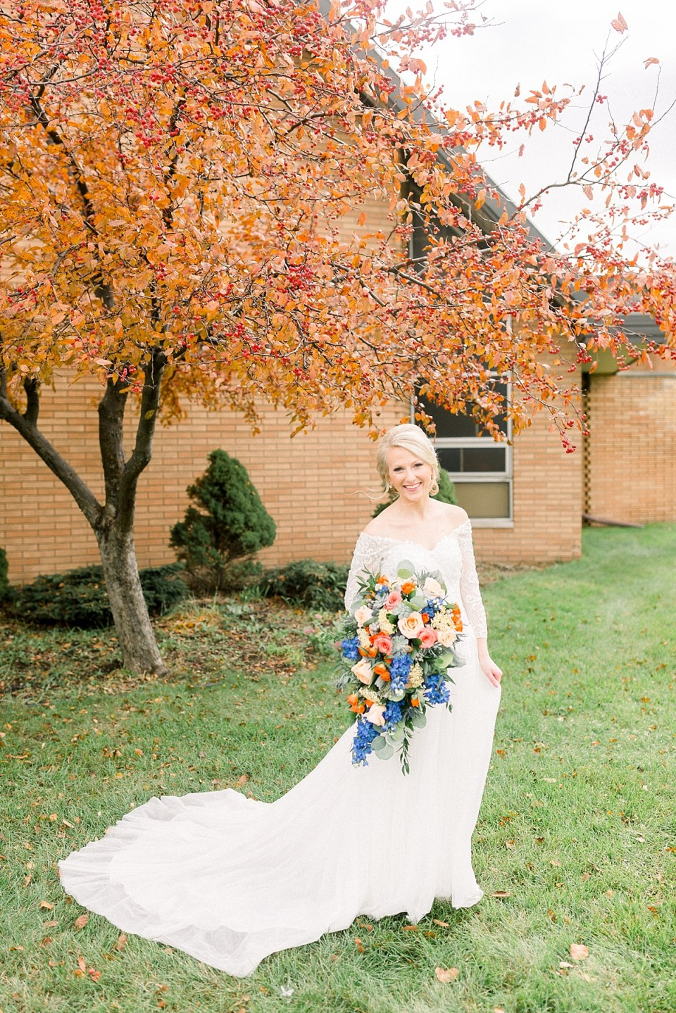 Arielle Peters Photography | Bride smiling with her bouquet outside next to bright orange tree on fall wedding day.