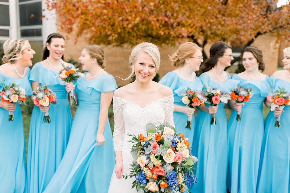 Arielle Peters Photography | Bride and bridesmaids smiling with bouquets outside on fall wedding day.