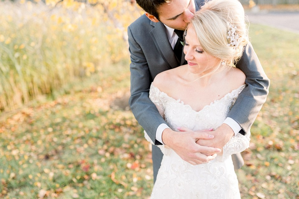 Arielle Peters Photography | Groom kissing the bride's forehead outside in a field on fall wedding day.
