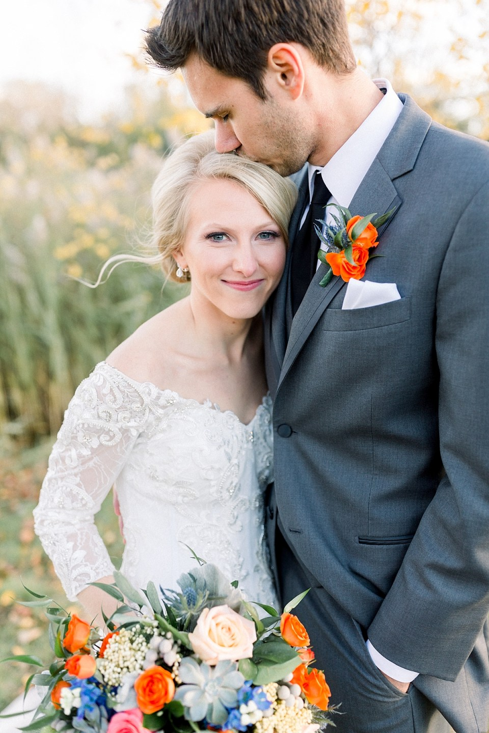 Arielle Peters Photography | Groom kissing the bride's head outside in field on fall wedding day.