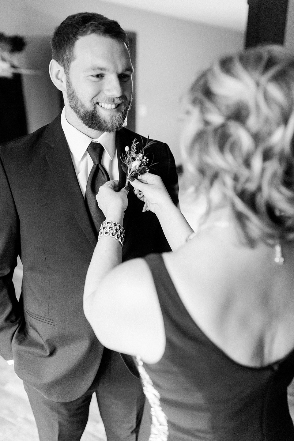 Arielle Peters Photography | Groom putting on boutonniere on wedding day.
