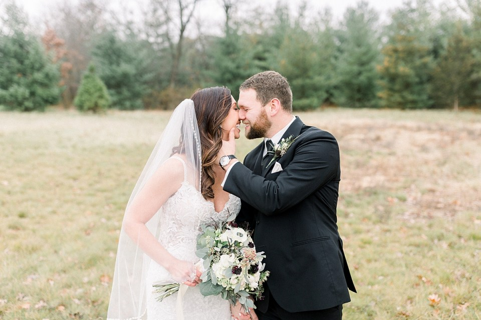 Arielle Peters Photography | Bride and Groom in field kissing on wedding day.